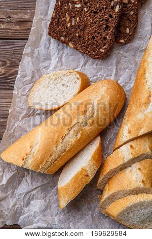 Fresh baguette and black bread with sunflower seeds on wooden table