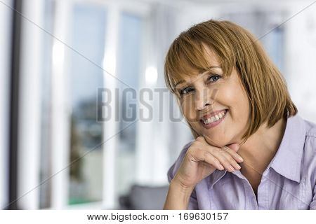 Portrait of happy woman with hand on chin at home