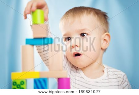 Portrait of a two years old child stocking wooden cubes. Pretty little boy on blue background