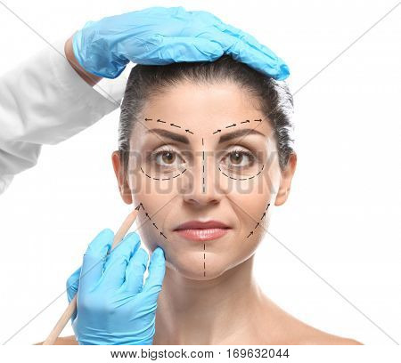 Surgeon drawing marks on female face against white background. Plastic surgery concept