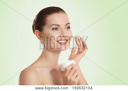 Young beautiful woman with facial cream on light green background. Skin care concept
