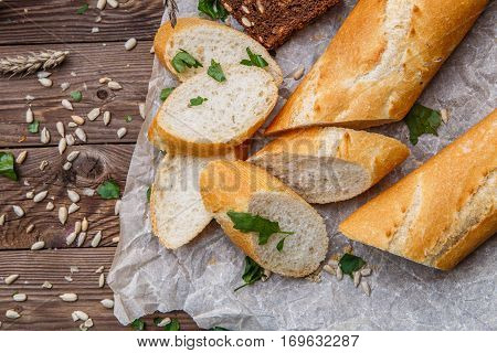 Cut bread on table with seeds and paper