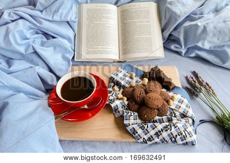 Breakfast served in bed - coffee, chocolate cookies, chocolate, hazelnuts on a wooden board on background of light blue bed linens, open book and bunch of lavender. Festive breakfast in bed concept.