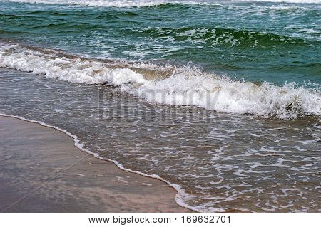 The restless waves of the sea with splashes at the beach close up