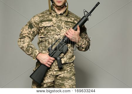 Soldier with assault riffle on grey background