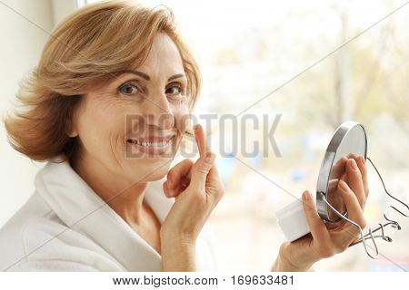 Gorgeous senior woman applying anti-aging cream on her face