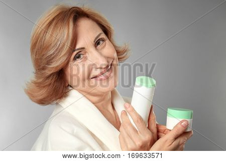 Gorgeous senior woman holding anti-aging cosmetics on grey background