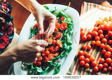 Preparation of fresh salad with tomato ruccola on the kitchen table.