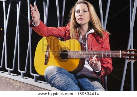 Caucasian Blond woman Posing in Red Leather Jacket and Jeans with Guitar Outdors on Dark Street. Horizontal Image Orientation
