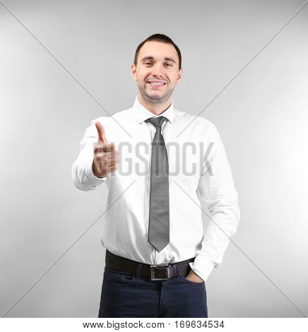 Handsome man showing thumb up sign, on light background