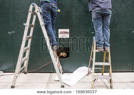 Two Handymen On Ladders