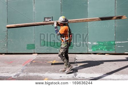 Worker In Overalls Carries Boards At The Construction Site