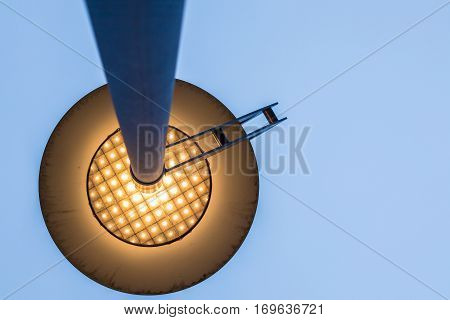 view under from a head street lamp on with with the clear blue sky at dusk as background