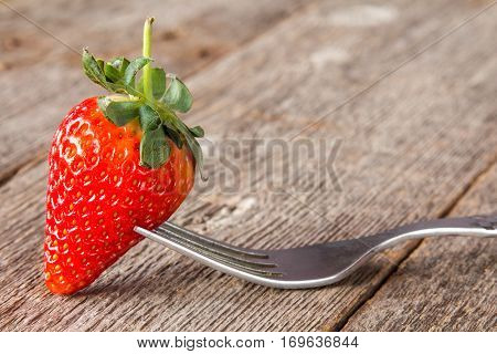 Fork with fresh strawberry ready to eat