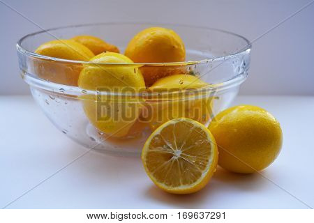 bowl of lemons on a white background and a lemon wedge