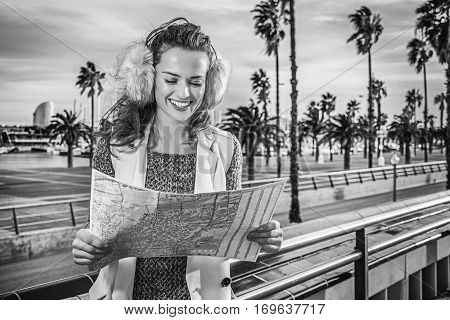 in Barcelona for a perfect winter. happy modern woman in earmuffs in Barcelona Spain looking at the map
