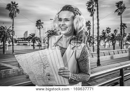 in Barcelona for a perfect winter. happy trendy woman in earmuffs on embankment in Barcelona Spain with map looking into the distance