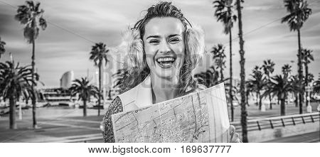 in Barcelona for a perfect winter. happy young tourist woman in earmuffs in Barcelona Spain with map