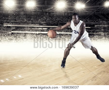 Strong and athletic African American basketball player dribbling the ball down the court during a professional basketball game in a large sports arena