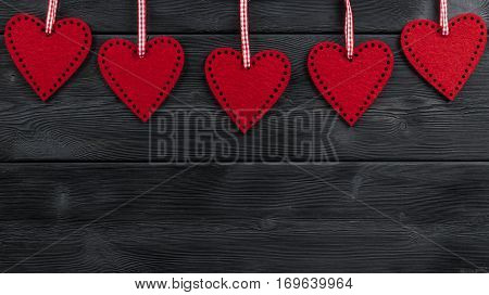 red hearts on the black rustic wooden background with woodgrain texture
