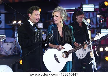 NEW YORK-DEC 31: Host Ryan Seacrest (L) and recording artist Carrie Underwood onstage during Dick Clark's New Year's Rockin' Eve at Times Square on December 31, 2015 in New York City.