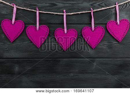 pink hearts on the black rustic wooden background with woodgrain texture