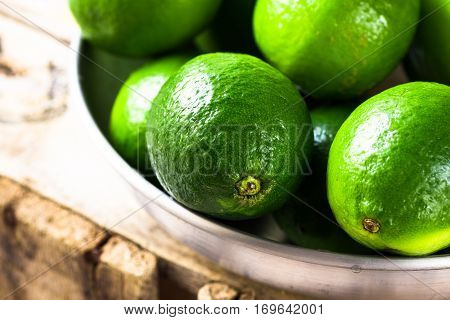 Heap of ripe colorful limes in aluminum dish on wood box, sunlight, freshness, health concept, detox drink ingredient