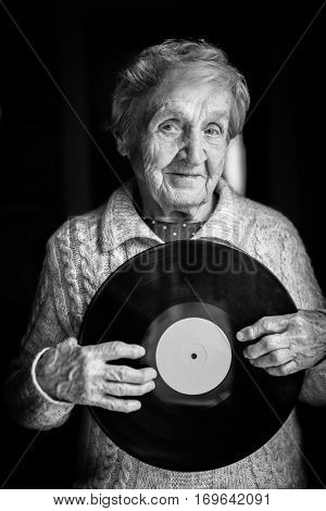 Elderly woman is holding a vinyl record. Black and white photo.