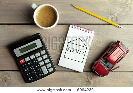 Notepad with loan question inside a sketch of a house with a miniature car and calculator