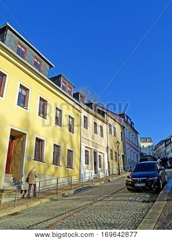 Annaberg-Buchholz, Germany - December 20, 2015: A woman walking up a steep road in the old town of Annaberg-Buchholz (Germany) along beautifully restored houses.