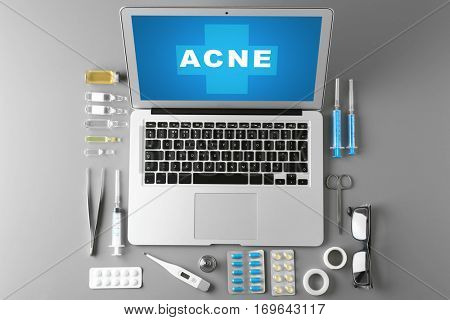Dermatologist equipment on gray background. Word ACNE on laptop screen