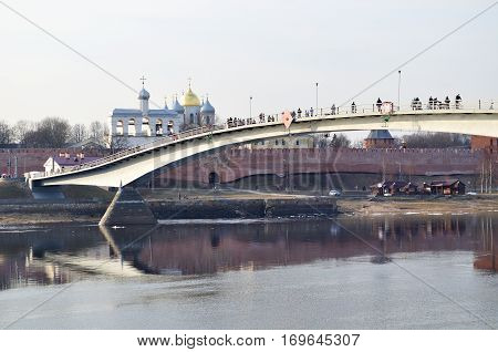 Architecture spring Russian landscape - Novgorod Kremlin in Veliky Novgorod, Russia and footbridge across the Volkhov river in spring sunset evening. Architecture landscape of Russian landmarks