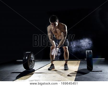 closeup of weightlifter clapping hands before heavy deadlift exercise at the gym