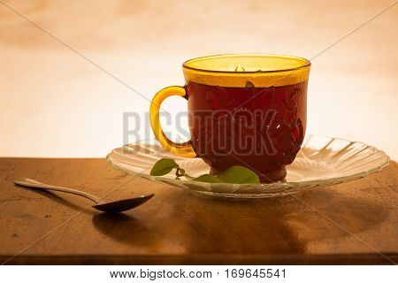 cup of tea shot against a backlit wooden background