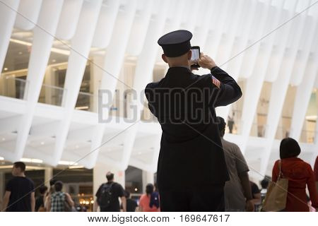 NEW YORK - SEPT 11 2016: People take pictures of the Freedom Tower from the main concourse of the Oculus, the new World Trade Center transit hub on the 15th anniversary of the 911 terror attack.