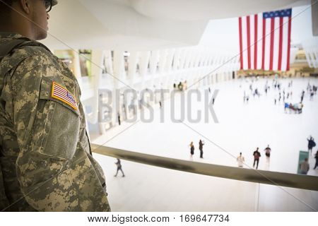 NEW YORK - SEPT 11 2016: Military personnel on patrol look down on the mezzanine of the Oculus structure to the center of the main transit hall of the World Trade Center transit hub in Manhattan.