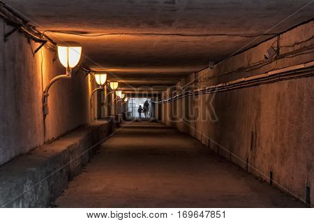 Silhouette of a mother and child crossing an empty subterranean passage. Underground tunnel.