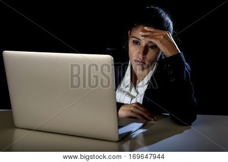 young latina business woman or student girl working in darkness on laptop computer late at night looking concentrated and tired in long hours of work concept isolated on black background