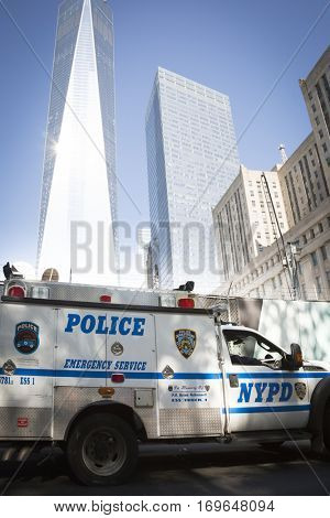 NEW YORK - SEPT 11 2016: A NYPD truck drives by the World Trade Center sign on the fence along Church St at the construction site for Tower Two in the new WTC complex.
