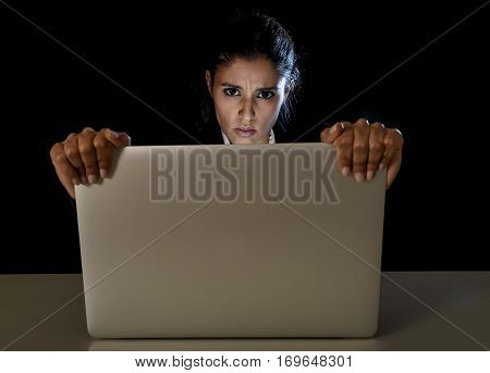 young business woman or student girl working in darkness holding laptop computer screen late at night in stress and tired in long hour of work concept isolated on black background