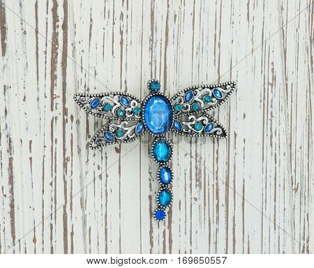 brooch in the form of dragonfly on wood