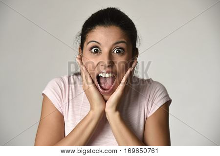 head portrait of young beautiful Spanish surprised woman amazed in shock and surprise happy and excited isolated grey background in astonished wow face expression