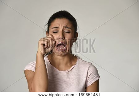 young beautiful latina sad woman serious and concerned crying desperate overacting on feeling depressed isolated grey background in sadness and sorrow emotion