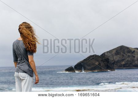 girl looking at atlantic ocean waves volcanic island nature Portugal Azores travel landscape wind hair back