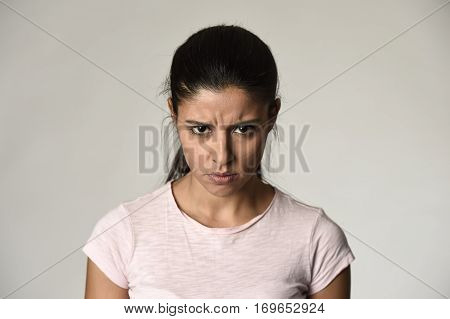 head portrait of young beautiful latin angry and upset woman looking furious and crazy moody in intense look and rage face expression isolated grey background in anger emotion concept