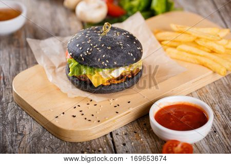 Black Hamburger With Bacon And Sauce On A Wooden Stand