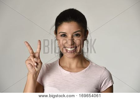 portrait of young beautiful and happy Latin woman with big toothy smile excited and cheerful in charming face expression giving hand victory and peace sign isolated clear grey