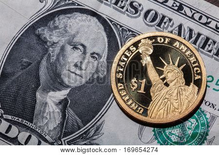 One dollar coin - The Statue of Liberty - on one dollar banknote. Closeup, macro shot