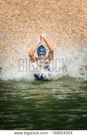 Triathlete in training running into water, colo image