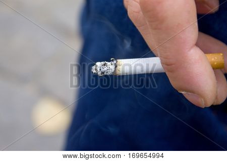 Cigarette in hands smoke from a cigarette close up